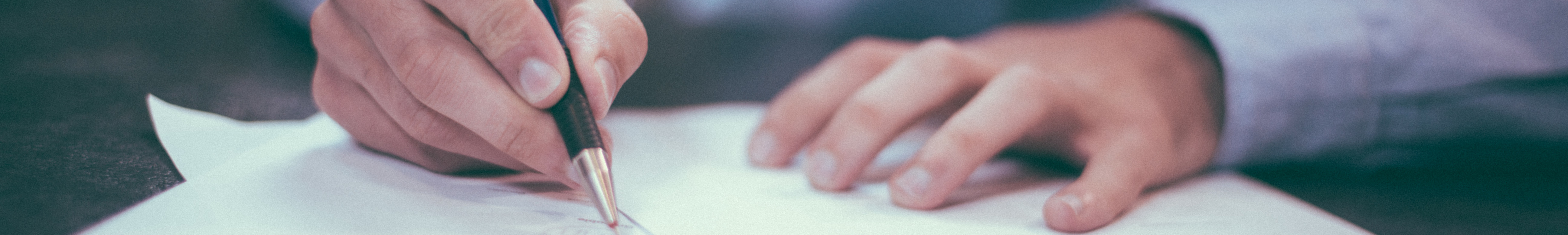 Hands holding pen writing on a piece of paper