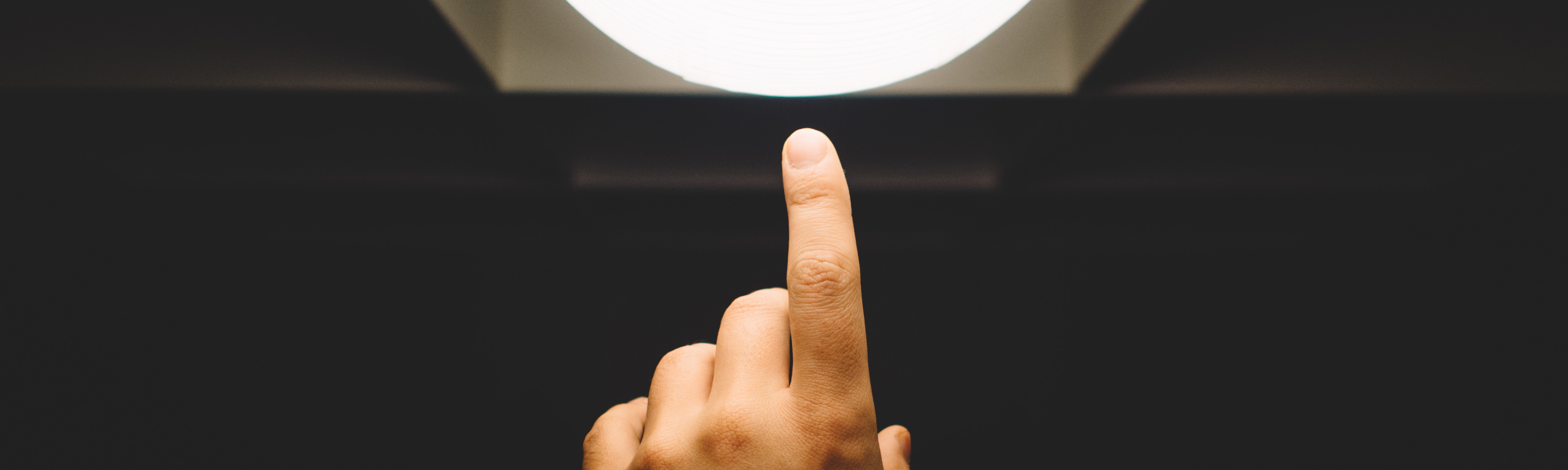Finger pointing at a light-bulb in a darkened room, suggesting innovation.