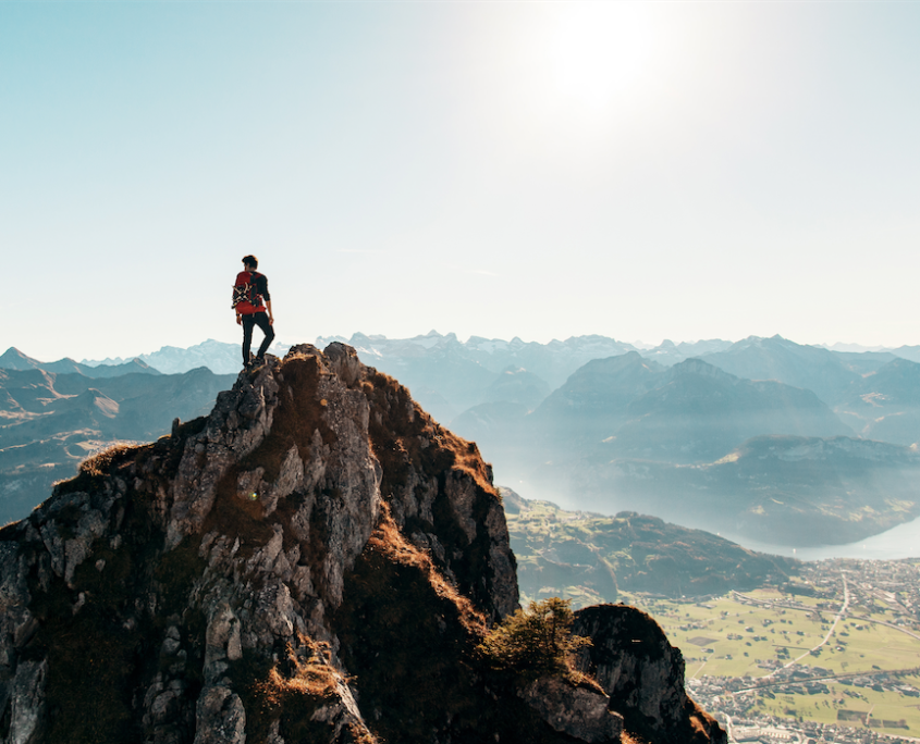 Rock climber standing at the top of a mountain, overlooking the valley below