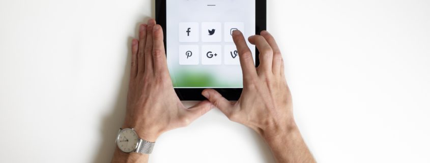 Person holding tablet with icons of social media platforms on the screen